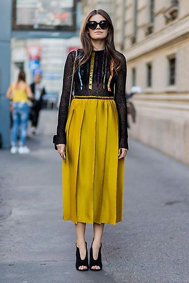 Falda midi de color mostaza con transparencia en negro
