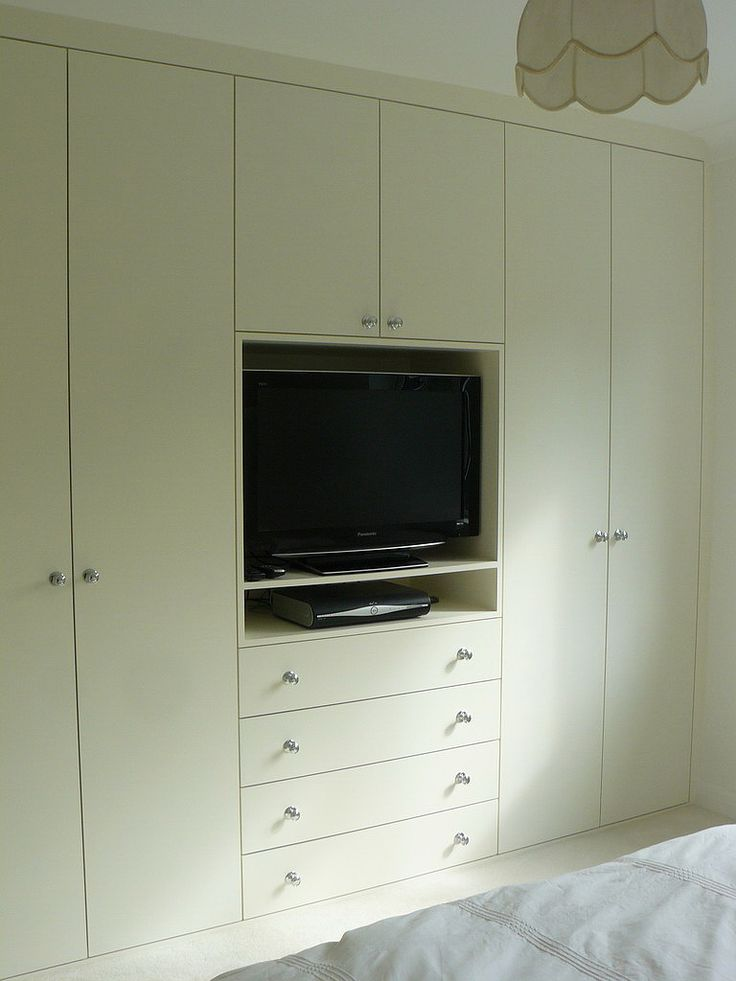 don't like look of these wardrobes, but good example of central exposed TV between wardrobes