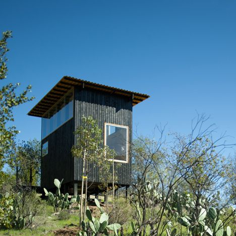 This charred timber cabin by Chilean studio DRAA is raised over a hillside on stilts to afford better views of the nearby mountains.