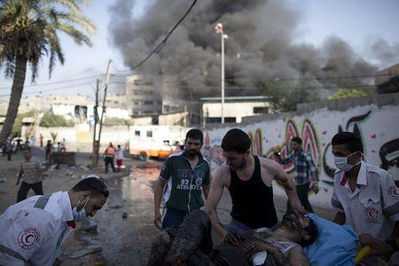 30日、ガザ市東郊シェジャイヤ地区で、イスラエル軍の空爆で負傷した男性を運ぶ赤新月社の救助隊(AFP=時事) ▼31Jul2014時事通信|ガザ攻撃継続の構え=停戦模索の動きも-イスラエル http://www.jiji.com/jc/zc?k=201407/2014073100083