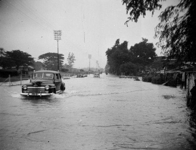 Auto rijdt in overstroomde straat na moessonregen in Surabaya, Indonesië (1950)