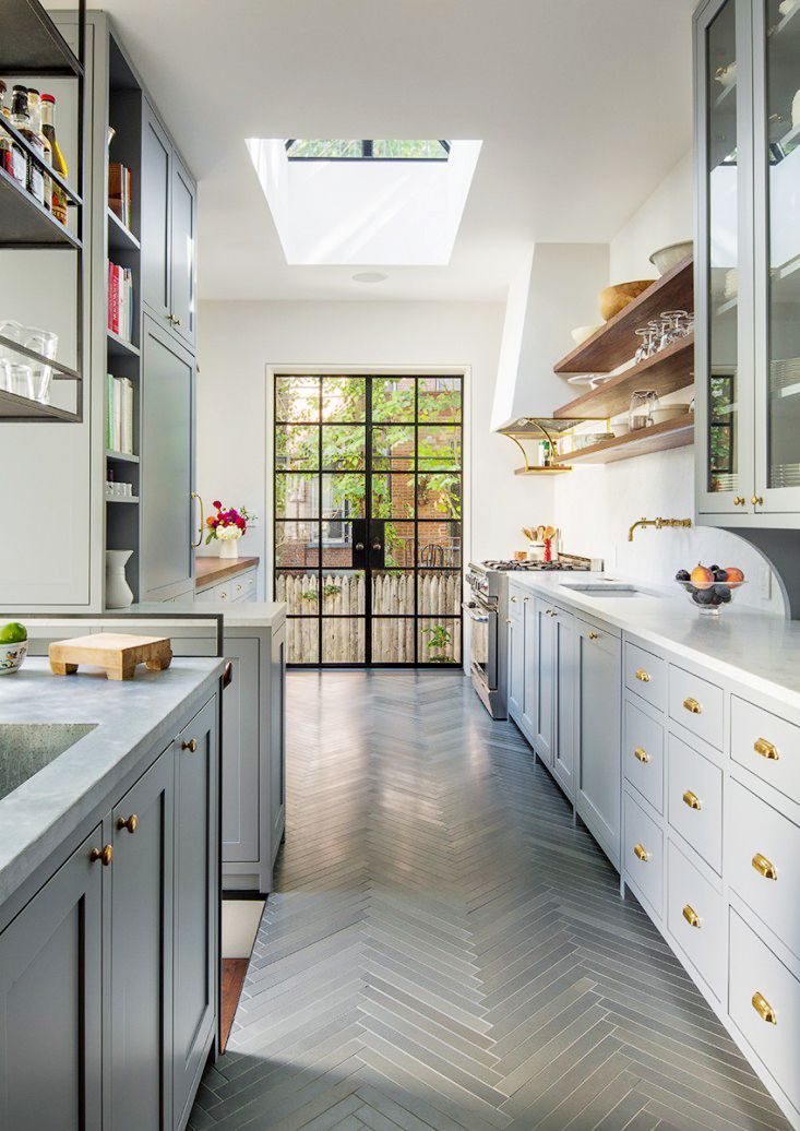 Bright galley style kitchen with gray herringbone floors, brass hardware, skylight, & floating shelves