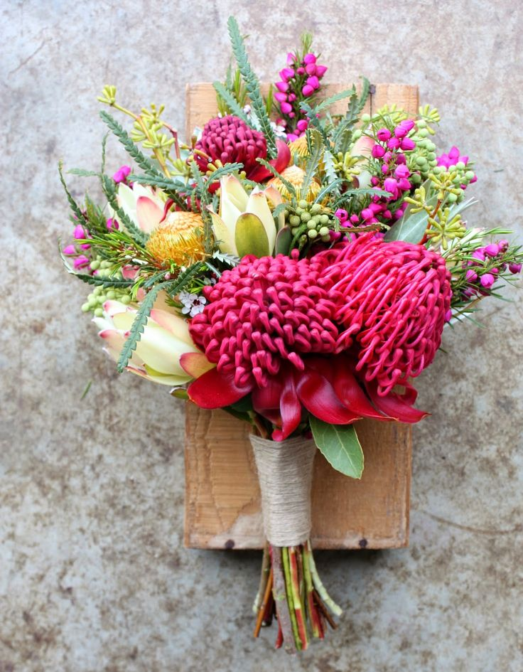 This Bouquet features Red Waratahs at the front and cream Proteus. Banksia and banksia leaves., and green/yellow gumnuts. The deep pink little flowers are unknown to me.