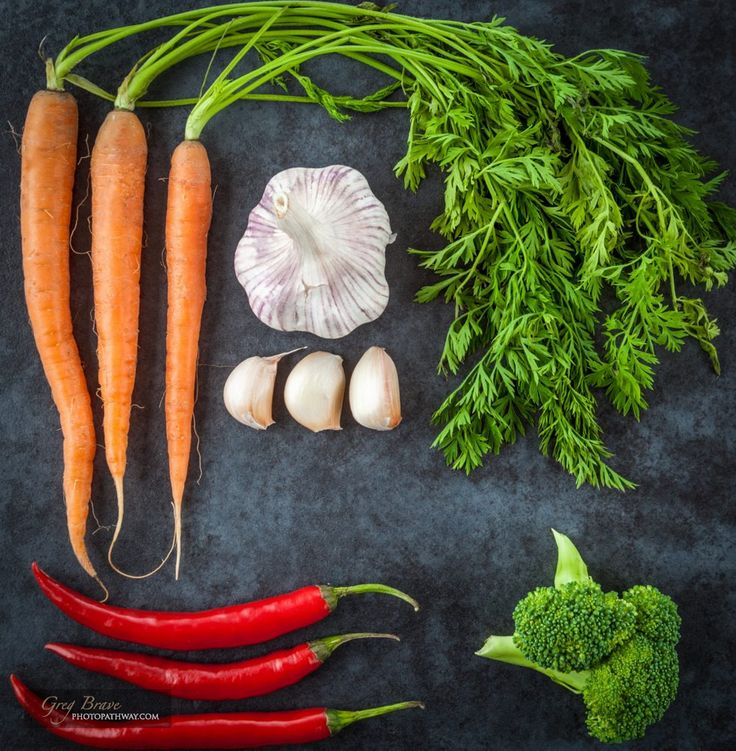 Hot chili peppers, Dutch sweet carrots, broccoli, and garlic creatively arranged on grunge background. Top view.