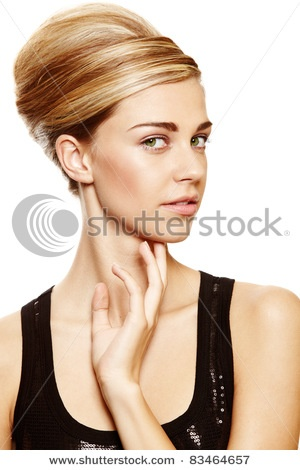 Beautiful blond woman with natural make-up wearing hair in a classic french roll updo hairstyle over white studio background