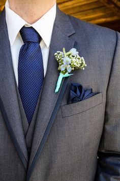 Groom in dark gray suit + navy blue tie and pocket square + baby's breath…
