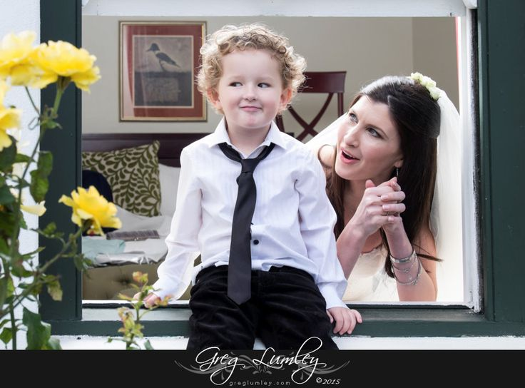 Mischievous young ring bearer with bride on windowsill