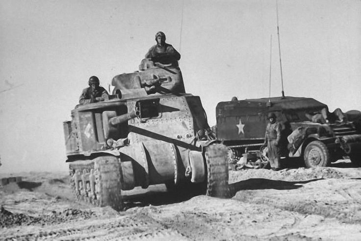 an m3 lee medium tank of company i 13th armored regiment 1st armored division passes a communications half track near sened tunisia in 1943