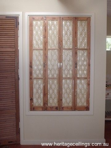 These pressed tin Fishscale panels were given an aged appearance using paint and then installed in screen doors.
