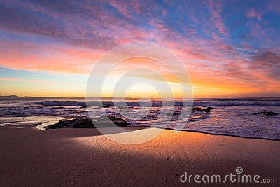 Dawn at this beach shows brings color and contrasts for a few amazing minutes. Photo image captured before sunrise on the beach with the rocks and small waves washing up the reflecting sand and coastline becoming natures canvas