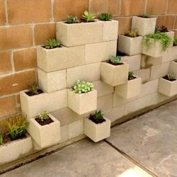 I totally want this in my garden! its a planter made of cinderblocks stacked against the wall in a very unique way.