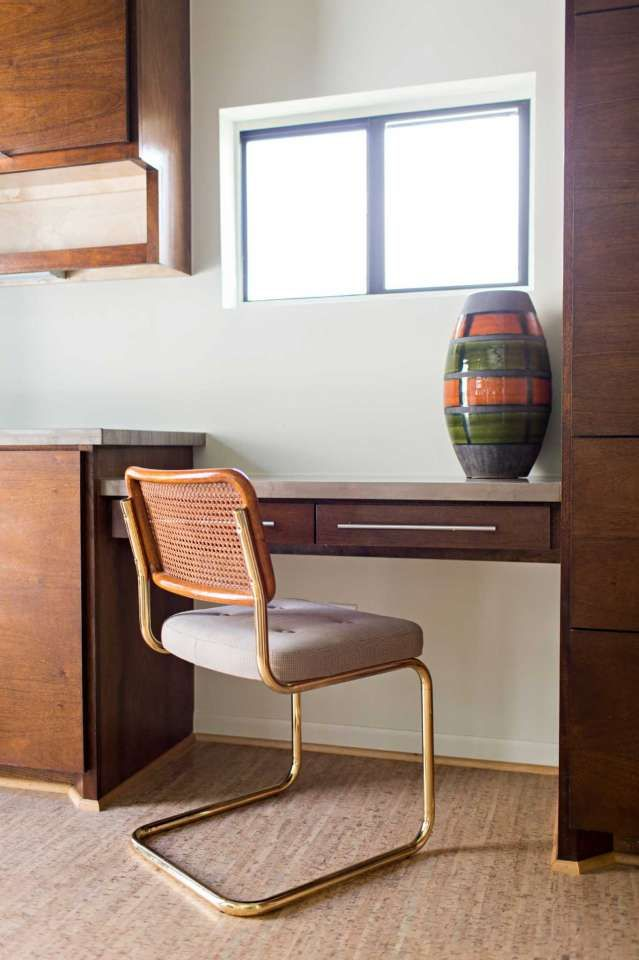 A cantilevered chair decorates the former pantry, which was turned into a mud room and small office area off the kitchen.