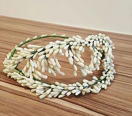 """Corona de porcelana de una arcada confeccionada con pistilos en colores blanco roto y verde tierno, montada en hilo de seda verde hierba de """"Winter 109""""."""