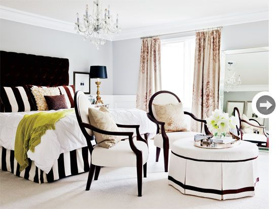 """Irene went for drama in the dream master bedroom with a tall tufted headboard in a dark rich chocolate velvet, along with bold striped throw pillows and a matching bedskirt. Pale blue-grey walls and overscale damask patterned drapes soften the """"masculine"""" feel and add to the luxury, as do the plush creamy white carpet, bevelled floor mirror and stunning chandelier."""