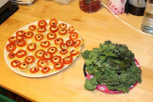 Gebackene Kartoffelchips mit frischer Tomate, Granatapfelkernen, frischen Grünkohl, Brennesselsamen und einem Orangen-Tahini Dressing