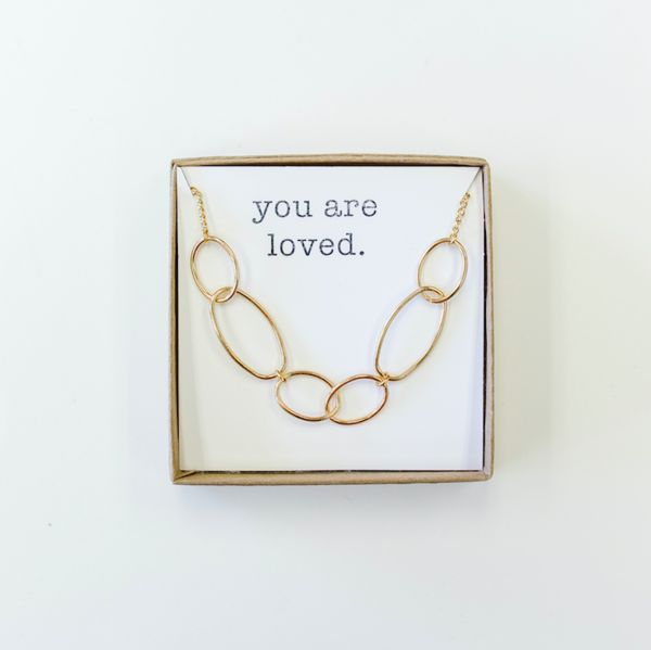 "Part of the Touch the Sky Collection, our gold Love Chain Necklace features a toggle clasp and hangs approx. 18"". It is a simple addition for most necklines and is perfect for layering. The compliment in the box can be customized making it the perfect gift."