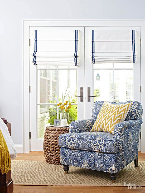 Crisp Roman shades cover French doors in this sunny nook. To add a little flair to plain white fabric, a ribbon of blue trim runs a vertical path down each side, tying the window treatment with the chair upholstery. Grosgrain ribbon applied with a hot-glue gun is an easy no-sew alternative for do-it-yourselfers.