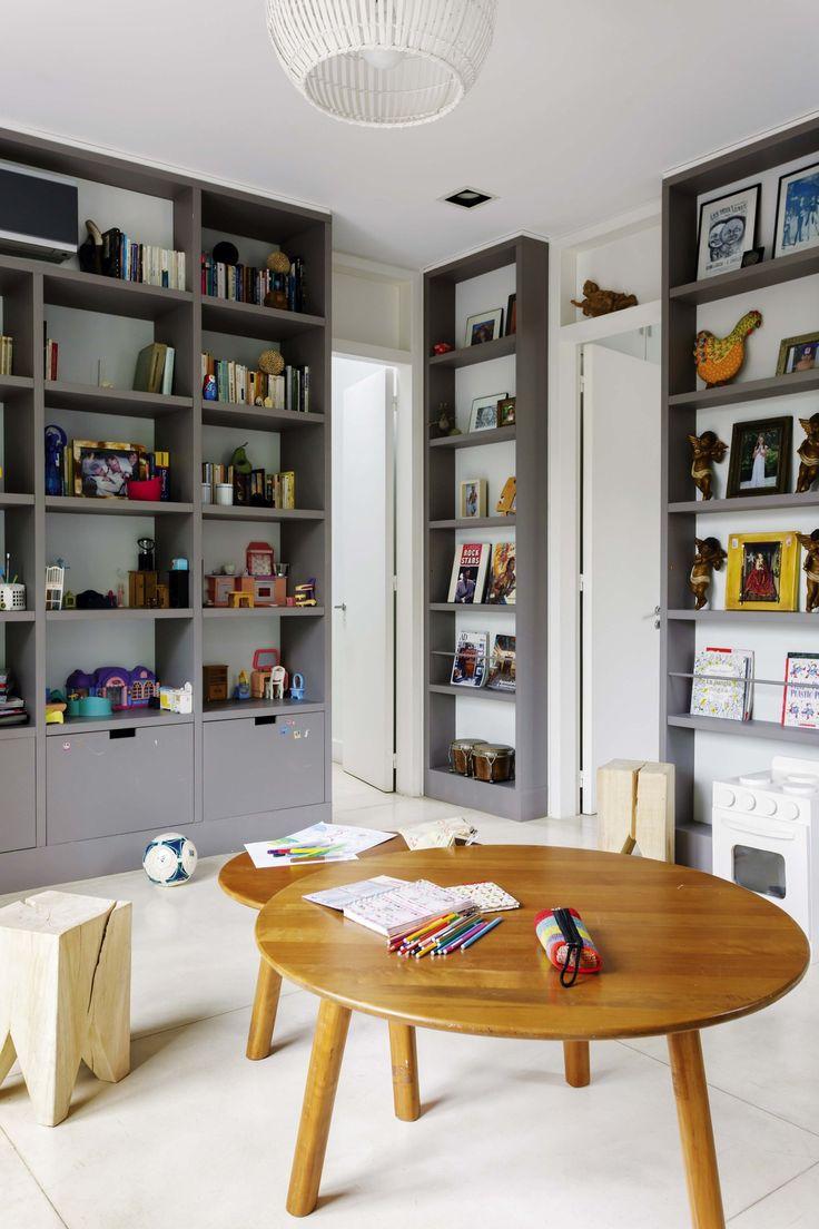 En el Playroom de la casa de María Freytes, estanterías con cajones bajos para juguetes, banquitos 'muela' (Las Marinas) y mesas redondas de madera (Desli) para sentarse a dibujar o leer.