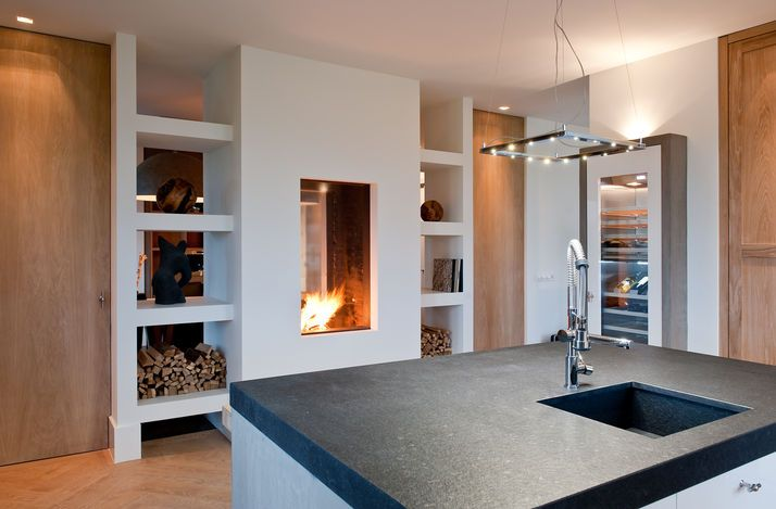 stunning lighting and glamorous fireplace in this contemporary kitchen - white granite grey and wood - Derk