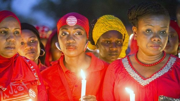 Nigerians hold candles during a vigil for the one year anniversary of the kidnapping of hundreds of Nigerian school girls in Chibok, Abuja, Nigeria, 14 April 2015