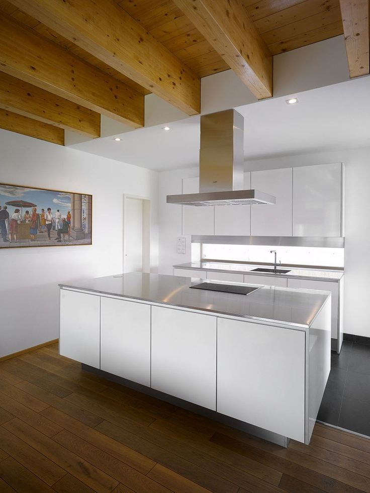 Family House In Klokočná By Studio Pha   Gluelam Wood Beams Merging Into  White Kitchen False Ceiling. Note: White And Stainless Steel Kitchen.