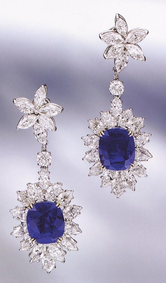 PAIR OF SAPPHIRE AND DIAMOND PENDANT-EARCLIPS, HARRY WINSTON. The pendants set with 2 cushion-shaped sapphires weighing 15.61 and 16.16 carats respectively, framed by diamonds and supported by star-shaped diamond clusters at the top, the whole set with 24 marquise-shaped, 16 pear-shaped and 2 round diamonds weighing a total of approximately 22.70 carats, mounted in platinum, stamped with hallmark for Winston, pendants detachable.