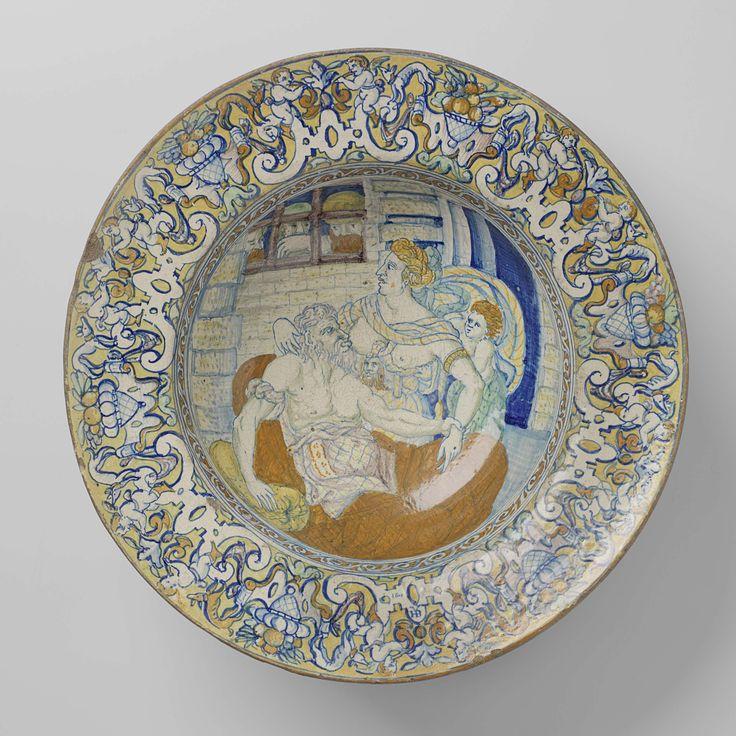 Hans Bernaert Vierleger | Schotel met Cimon en Pero, Hans Bernaert Vierleger, 1601 | Schotel van aardewerk, aan voor- en achterzijde met tinglazuur gedekt. Aan de voorzijde in het plat veelkleurig de voorstelling van Cimon en Pero (Caritas Romana). In de kerker geeft Pero Cimon de borst. Het kind is op haar rug gebonden. Drie mannen kijken door een tralievenster. De kleuren zijn blauw, bruin, groen, geel en paars. Om de voorstelling een rand van gestileerde ranken in bruin en blauw. De rand…
