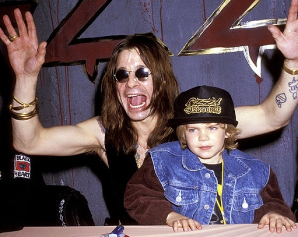 Ozzy Osbourne raises his hands behind a young Jack Osbourne in 1991.