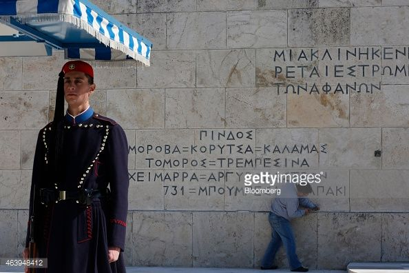 A marble craftsman carves Greek lettering onto the wall of a monument to the unknown soldier as an Evzones ceremonial guard stands on duty outside the presidential palace in Athens, Greece, on Friday, Feb. 20, 2015. Photographer: Kostas Tsironis/Bloomberg via Getty Images
