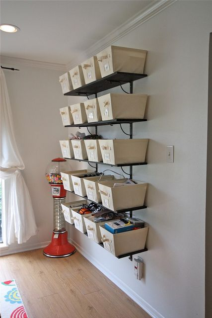 instead of shelving use a bookcase.  Smaller baskets/boxes up high marked with whats in them... like boning, leather tools, elastic, ribbon, adhesives, ect.  and larger boxes/baskets  on the bottom two shelves. It would work well for you if you left them empty and used them for project boxes that you can lable the project on the outside and just shove everything back in the box when you are doneskies