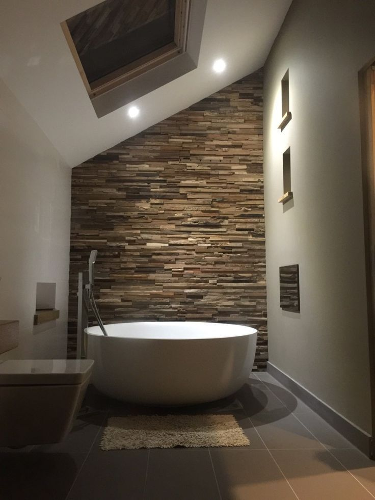 Badezimmer mit freistender Badewanne und einer XXL Wand mit Naturstein Bricks braun. #Bricks #Badewanne