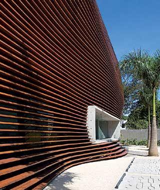 A membrana de madeira ora se afasta, ora se aproxima da edificação, conforme a demanda de proteção solar e acústica