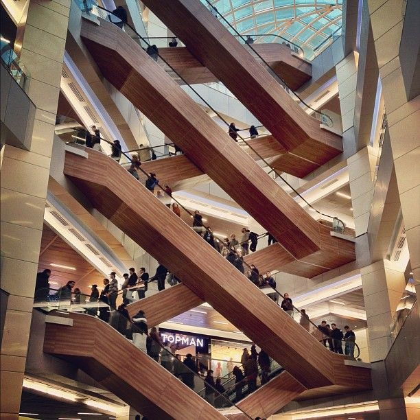Amazing architectural design: low-tech, natural wood wrapping and hiding high-tech escalators spanning multiple levels in a multi-story mall.