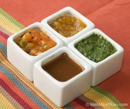 four types of chutneys: mango laced with saffron, tomato flecked with mustard, mint-cilantro, and sweet and spicy tamarind.