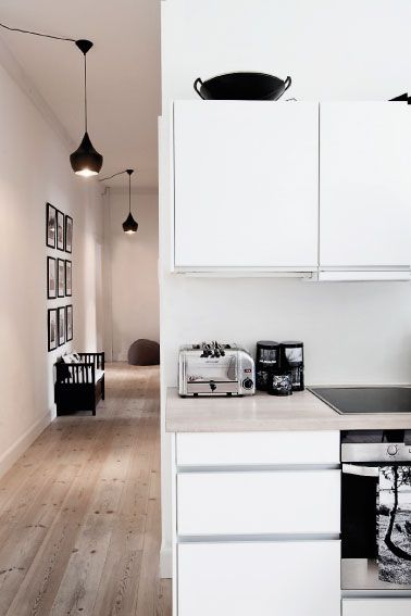 White Scandinavian kitchen, black and white and wood. Love the hallway pendant lights.