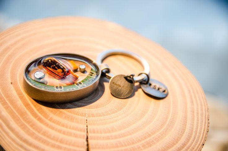 Brelok z wtopionymi w żywicy: fragmentem elektroniki modułu SAS (czujnika skrętu), pomarańczową żarówką kierunkowskazu lusterka bocznego i białą żarówką podświetlania przełącznika świateł Volvo #pARTs #KarlikArt #jewelry #Orska #upscaling #Volvo