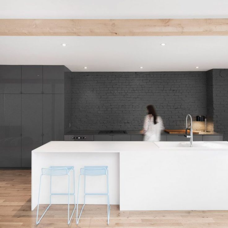 The kitchen area in this Montreal apartment by Anne Sophie Goneau is defined by shades of grey. A white island doubles up as a sink space and breakfast bar, while a more formal dining table is located behind a glass partition.