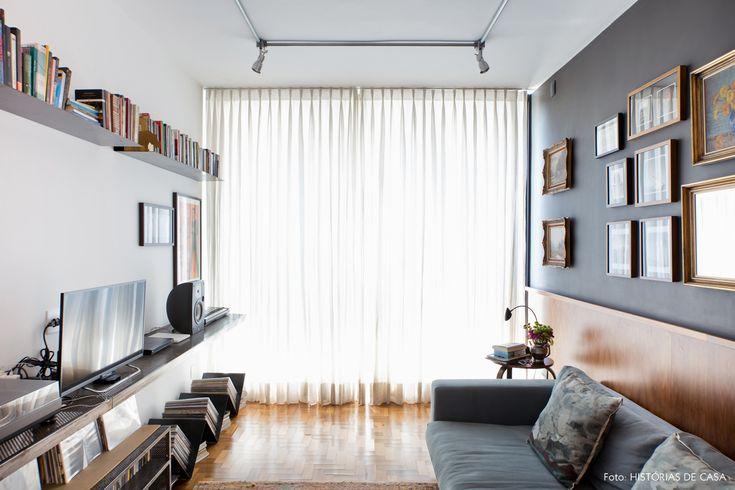 Estar com parede e sofá no tom de cinza e iluminação com tubulação à mostra.