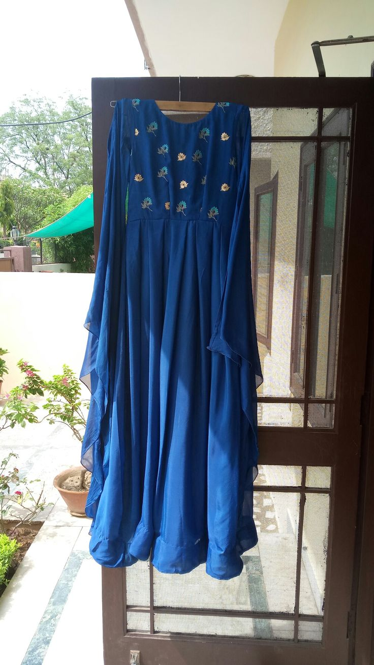 Blue chiffon crape dress with thread embroidery and golden pitton work on yoke and sleeves.