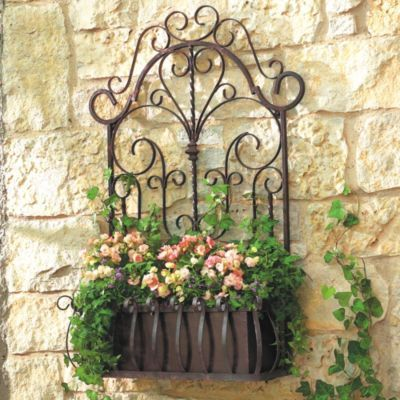Its delicate scrollwork and twisted rails were inspired by an antique garden gate. Handcrafted of wrought iron with removable metal planter. Weather resistant coating for use indoors or outdoors.