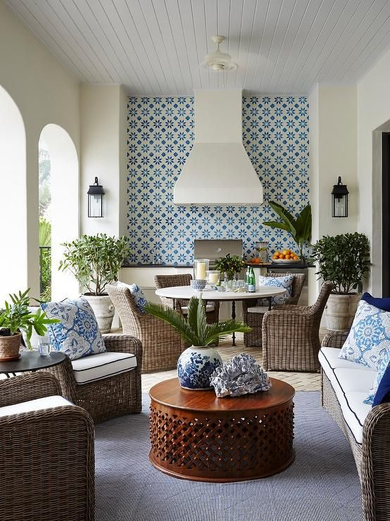 A covered patio kitchen features a white stucco vent hood lining a wall clad in white and blue spanish cement tiles, Classic Calais B Cement Tiles, and a stainless steel bbq grill illuminated by seeded glass carriage lanterns.