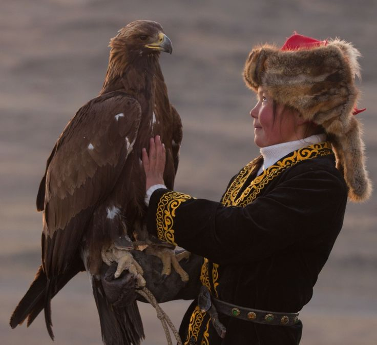 Eagle hunter Ashol Pan of Mongolia holds her golden eagle, giving perspective on the size of the eagle. Photo by Asher Svidensky/Caters News Agency