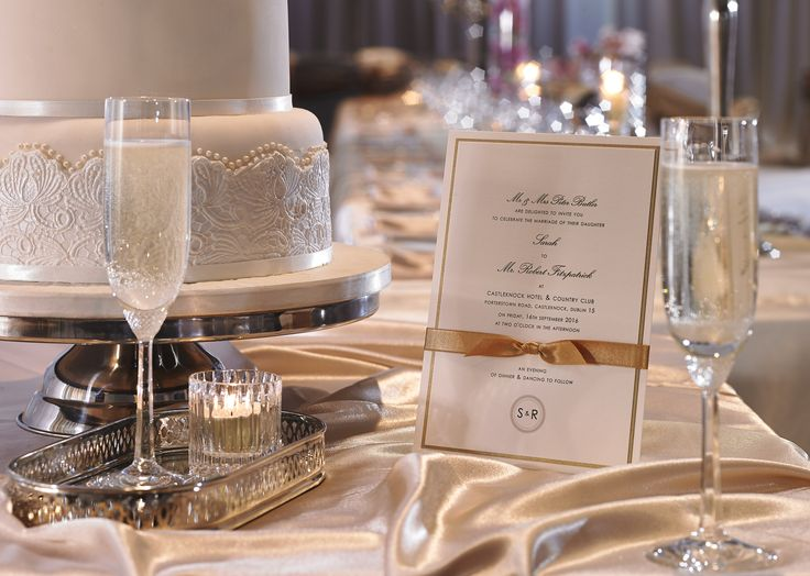 Closeup of wedding invitation, cake and champagne flutes