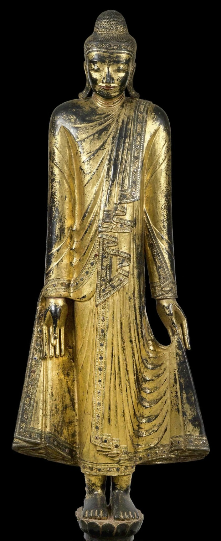 Burma: A large Buddha statue, standing on a lotus flower.  Wood, with black and partially red lacquer ground and gilding. The hair in small, thick nubs, with hemispherical 'ushnisha' on the head. In long robes with elaborate folds. The robe borders and the diadem over the brow decorated with small volute tendrils in gesso technique, as well as with rows and flowers made of round, white, red and green mirror plates.