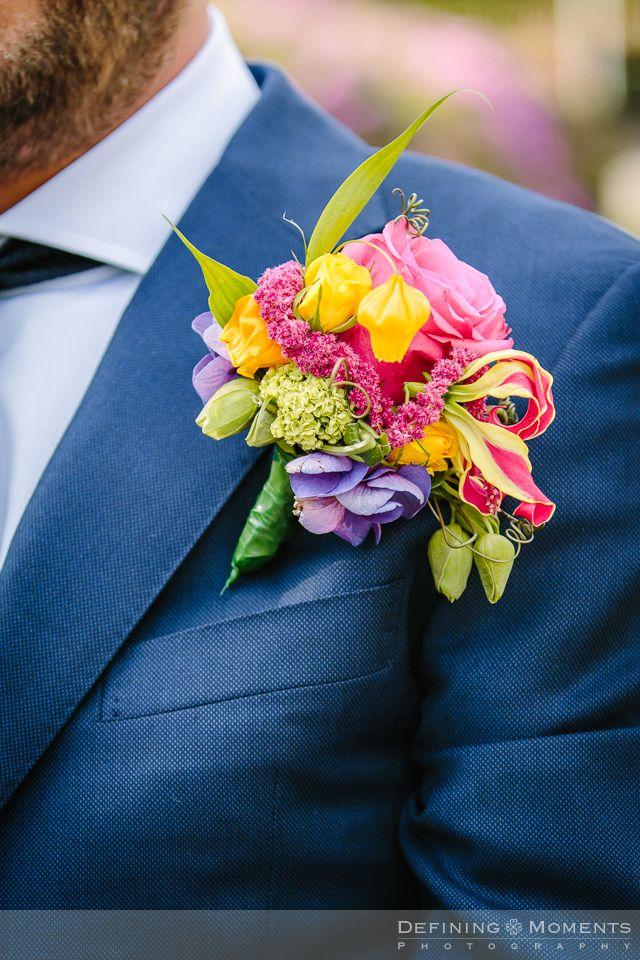 Bruidscorsage voor bruidegom in kleurrijke multi-color tinten met roze roos, paarse hortensia en roze gloriosa lelie, afgewerkt met oranje en zachtgroene accenten.