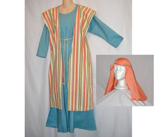 This is an Innkeepers Wife or shepherd costume for your Christmas Nativity Play. In stock and ready to ship.  The robe is robins egg blue cotton. The over robe is cotton with stripes in cream, corals, blue, yellow, and brown. Cotton/poly headscarf in coral.  This is approximately a girls size 12. The chest measures 38 inches, so will comfortably fit up to a 33 inch chest. The length is 49 inches from the shoulder to the hem. Easily shortened, but there is no extra fabric to let out in the…