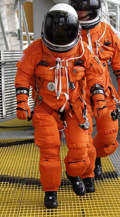 "An astronaut wearing the ACES suit The Advanced Crew Escape Suit (ACES) or ""pumpkin suit"",[1] was a full pressure suit that began to be worn by Space Shuttle crews after STS-65, for the ascent and entry portions of flight."