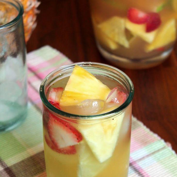 PINEAPPLE SANGRIA Recipe Cocktails, Beverages with pineapple juice, triple sec, white rum, honey, white wine, lemon, lime, strawberries, pineapple chunks