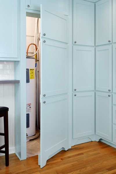 Faux cabinet doors hide a dedicated area for the water heater. Smart & looks great.
