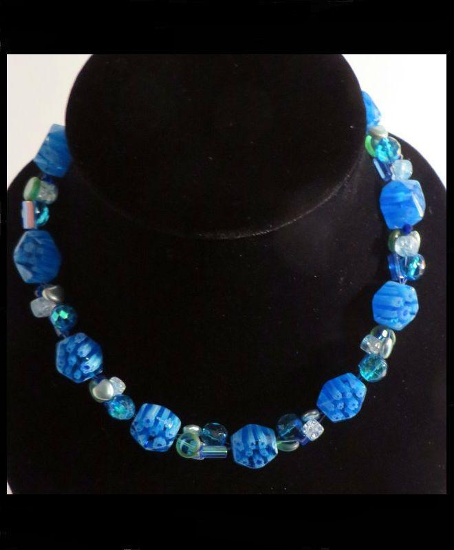 Blauw glazen ketting met bloemmotief.